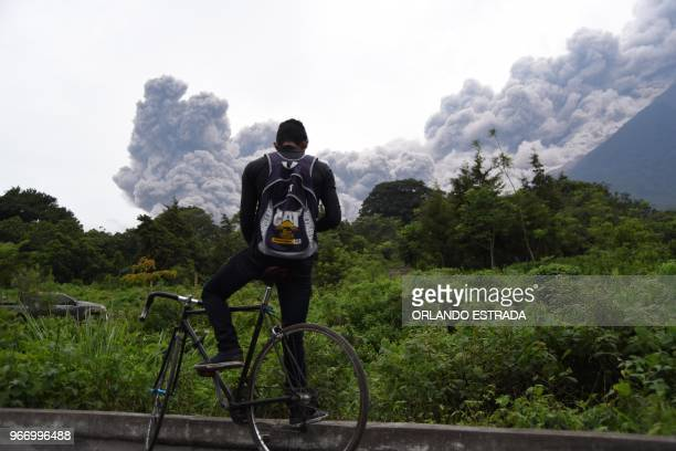 A man looks at the Fuego Volcano in eruption from Alotenango municipality Sacatepequez department about 65 km southwest of Guatemala City on June 3...