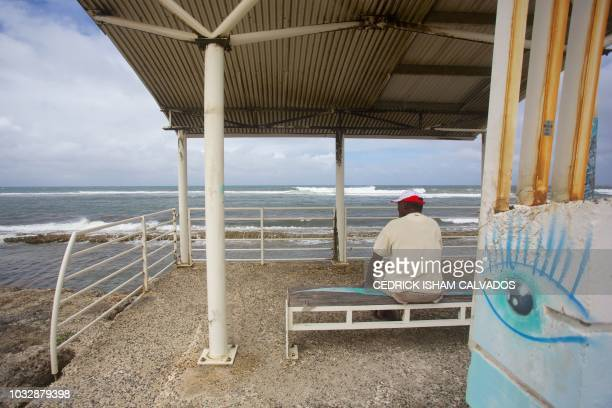 A man looks at the horizon on the beach in Le Moule on the GrandeTerre island of the French Carribean archipelago of Guadeloupe on September 13 as...