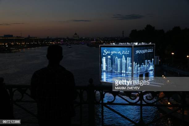 TOPSHOT A man looks at the illuminated walls of Majlis Qatar pavilion light in Moscow's Gorky Park in Moscow on July 12 2018 Qatar will host of the...