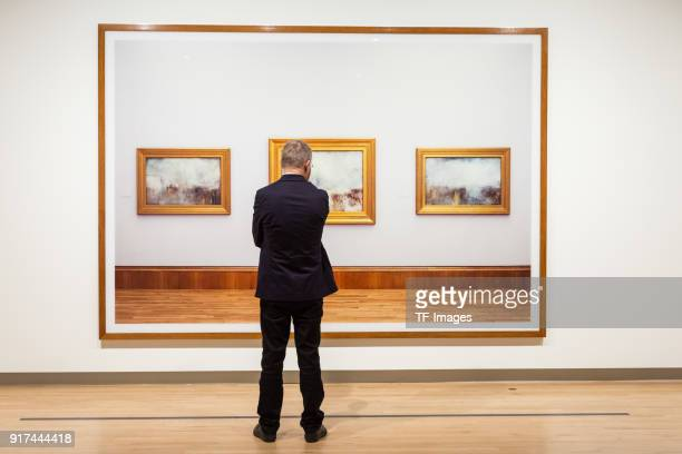 A man looks at the image entitled 'Turner Collection' by Andreas Gursky in the reopened Hayward Gallery on January 24 2018 in London England