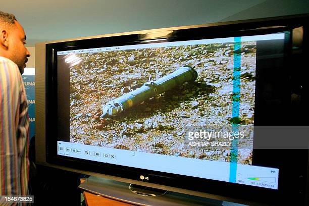 A man looks at the image of the remains of ammunition after a press conference held by Sudanese Culture and Information Minister Ahmed Bilal Osman in...