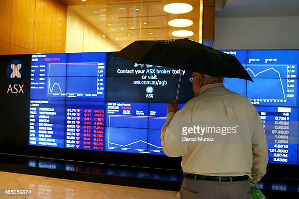 A man looks at the main board of the Australian Securities Exchange ASX displaying the main losses for the day on August 24 2015 in Sydney Australia...