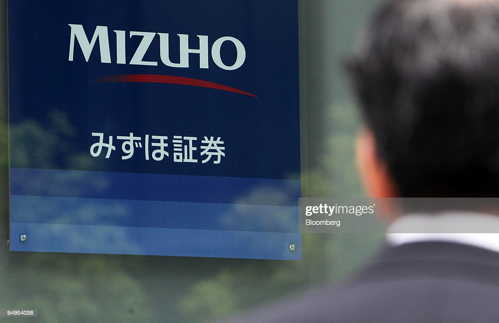 A man looks at the Mizuho Securities Co. logo, displayed out : News Photo