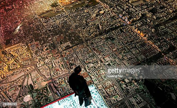 A man looks at the model of Beijing's city master plan which is 302 squares metres with the scale of 1750 as he visits Beijing Planning Exhibition...