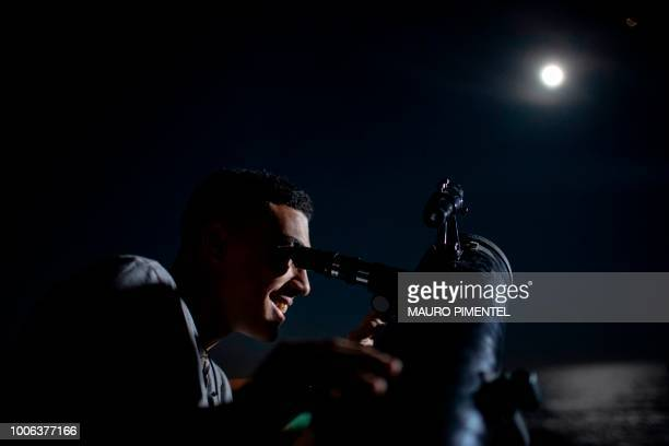 A man looks at the moon eclipse through a telescope at Copacabana Fortress in Rio de Janeiro Brazil on July 27 2018 The longest 'blood moon' eclipse...