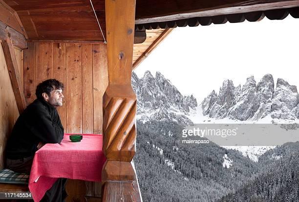 Homme se penche sur les montagnes depuis une cabine de montagne
