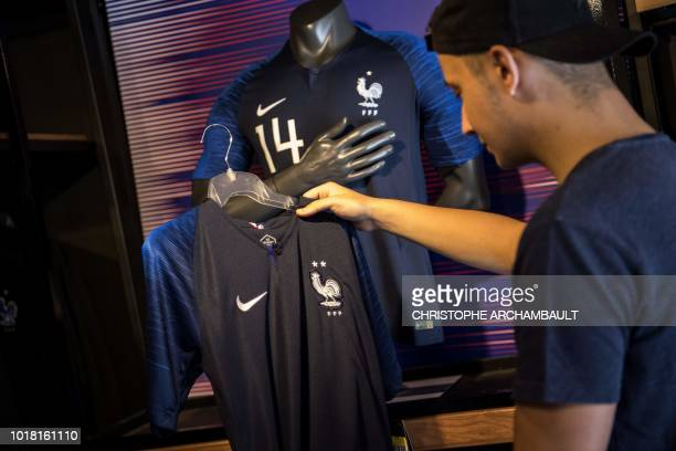 A man looks at the new jersey of the French national football team bearing the two stars of world champion displayed for sale at the French Football...