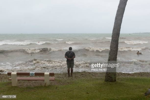 A man looks at the ocean in Anse Vata south of Noumea New Caledonia on March 14 2015 Rain and wind were observed in the island but the Tropical...