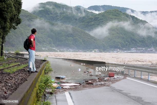 Man looks at the overflowing kuma river caused by heavy rain in Yatsushiro, Kumamoto prefecture on July 4, 2020. - Some 75,000 people were ordered to...