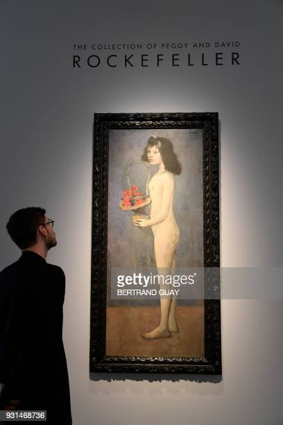 A man looks at the painting Fillette à la corbeille fleurie 1905 by late Spanish painter Pablo Picasso at Christie's France as part of a presentation...