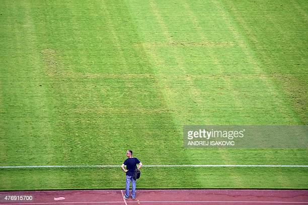 A man looks at the pitch appearing to show the pattern of a swastika following the the Euro 2016 qualifying football match between Croatia and Italy...