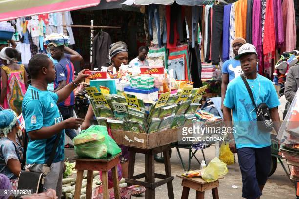 A man looks at the products displayed on a market stall selling rat poison at a steet market in Libreville on January 31 2018 The consumption of an...