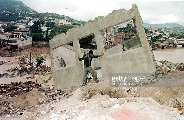 A man looks at the remains of the a building 11 November after Hurricane Mitch inundated the region and caused the Choulteca River to burst its banks...