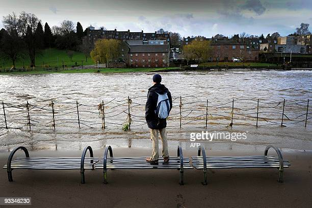 Man looks at the River Nith that caused floodings when it burst it's banks in Dumfries, south-west Scotland on November 22, 2009. Britain's flood-hit...