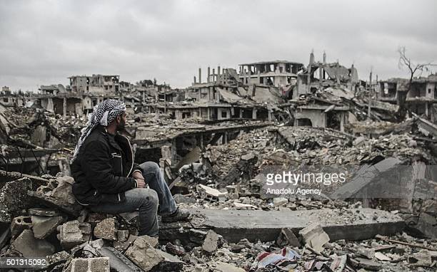 Man looks at the rubble of buildings destroyed in the clashes between DAESH militants and Kurdish armed armed groups in the center of the Syrian town...