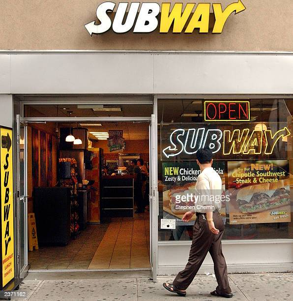 A man looks at the sandwich posters as he passes a Subway food store August 5 2003 in New York City Starbucks Coffee store chain has emerged as...