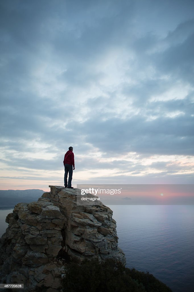 Man looks at the seascape from a cliff : Stock Photo