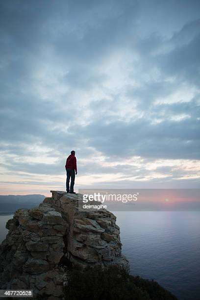 Man looks at the seascape from a cliff