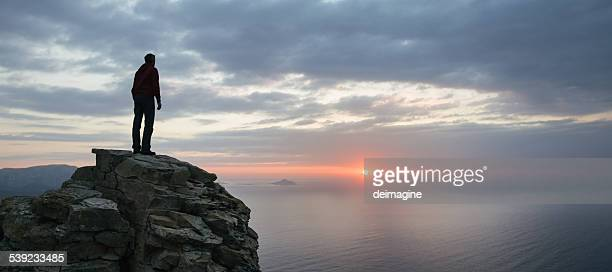 Man looks at the seascape panorama from a cliff