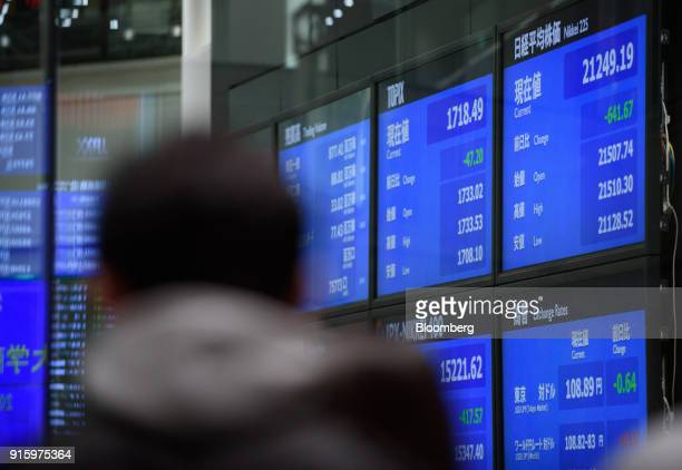 A man looks at the share prices displayed at the Tokyo Stock Exchange operated by Japan Exchange Group Inc in Tokyo Japan on Friday Feb 9 2018 The...