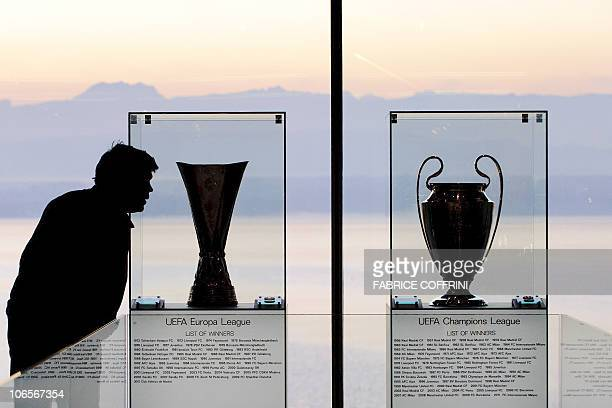 A man looks at the UEFA Europa cup trophy and the UEFA Champions League trophy prior to a meeting of the European football governing body UEFA on...