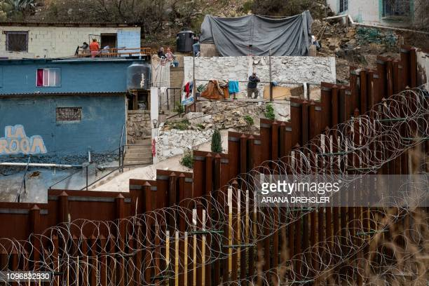 A man looks at the US/Mexico border fence covered in barbed/concertina wire from a house on the Mexican side as seen from Nogales Arizona on February...