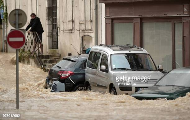 A man looks at vehicles trapped in flood waters that swept through the streets following heavy rains in SaliesdeBearn south western France on June 13...
