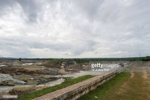 Man looks at water draining out of the collapsed section of Swar Chaung Dam spillway, seen at right portion at Swar township, Bago region on August...