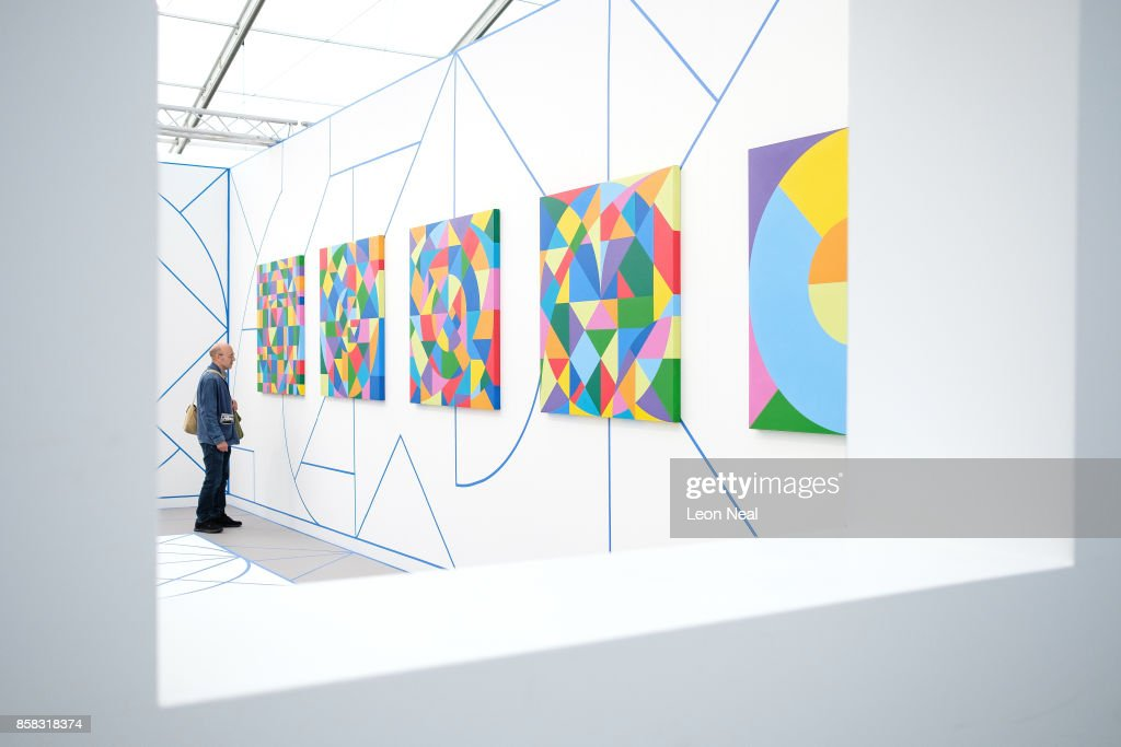 A man looks at works by Eduardo Terrazas at the Frieze Art Fair on October 6, 2017 in London, England. The annual event sees galleries showcase work by thousands of artists from around the world. The Frieze Art Fair runs from 5-8 October, 2017.