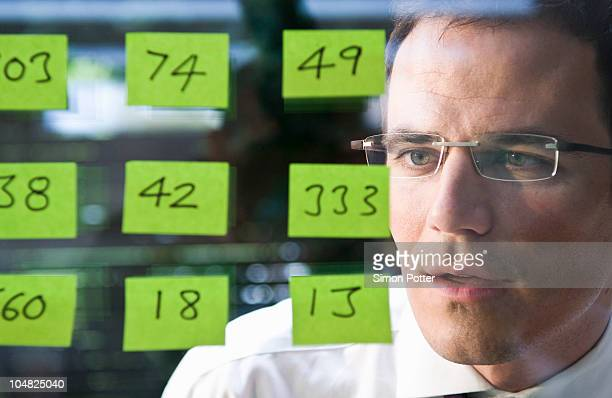 man looks at yellow stickers - groupe moyen d'objets photos et images de collection