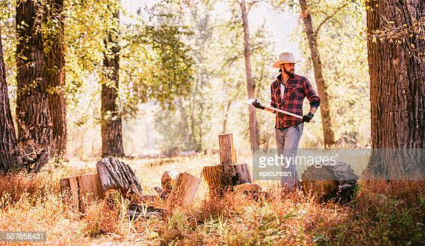 Man looks away while resting from chopping firewood in forest