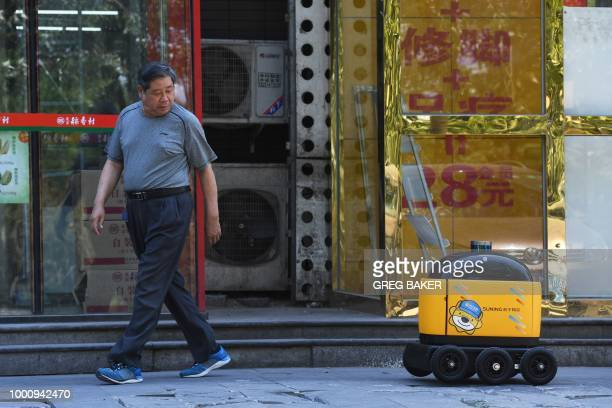 A man looks back at a Zhen Robotics delivery robot as it makes its way back to a supermarket after making a delivery during a demonstration in...