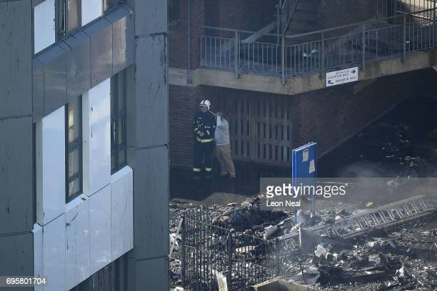 A man looks distressed as he speaks to a fire fighter after a huge fire engulfed the 24 storey residential Grenfell Tower block in Latimer Road West...