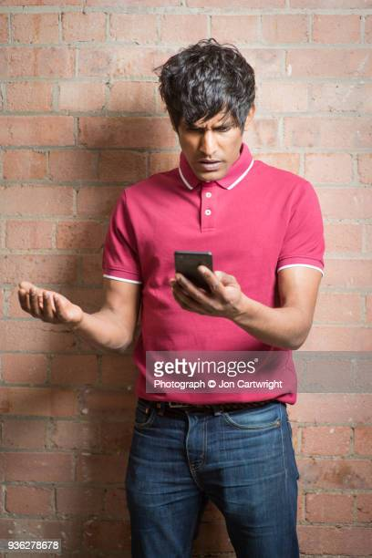 Man looks down at his phone with a look of disbelief