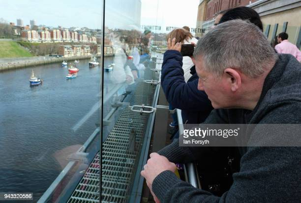 A man looks down from a viewing gallery in the Baltic Arts Centre as fishing boats sail up the River Tyne as fishermen take part in a nationwide...