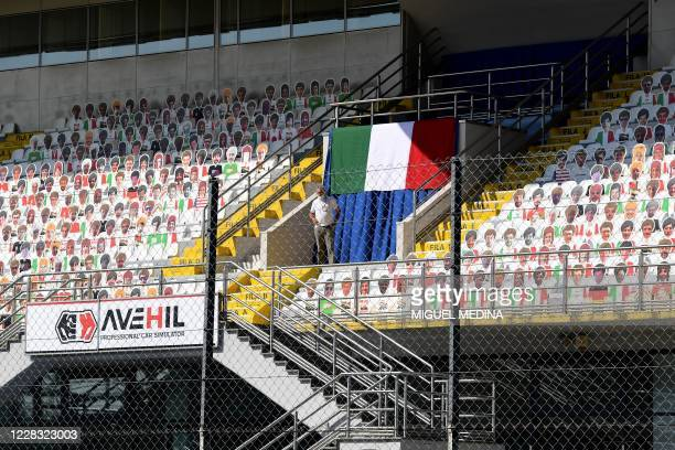 A man looks down from the stands with cardboard cutouts of visitors and the Italian national flag at the Autodromo Nazionale circuit in Monza on...