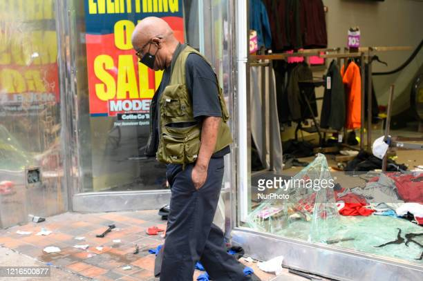A man looks down on the debris after looters gained access to numerous stores on Walnut Street in Center City Philadelphia Pa on May 30 2020...