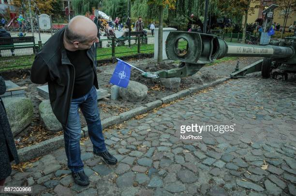 A man looks down the barrel of a Howitzer artillery gun on NATO day in Bydgoszcz Poland on October 14 2017