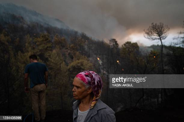 Man looks down where people use water to save a burning tree in Koycegiz district of Mugla, on August 3, 2021. - Turkey's struggles against its...