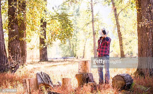 Man looks down while taking break from cutting firewood