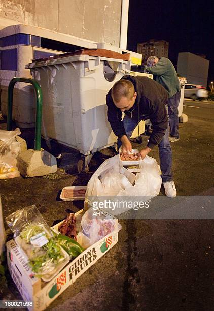 A man looks for food in a garbage container on January 16 2013 in Santa Cruz de Tenerife on the Spanish Canary Island of Tenerife Spain's...