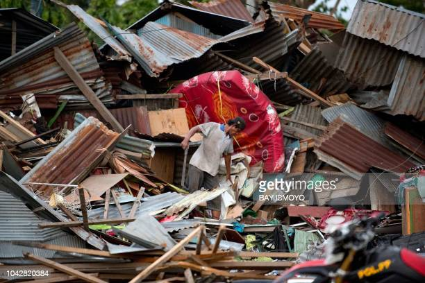 TOPSHOT A man looks for his belongings amid the debris of his destroyed house in Palu in Central Sulawesi on September 29 after a strong earthquake...
