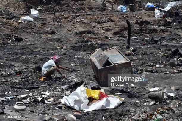 A man looks for his belongings at the fire site in which around 1000 shanties burnt down and turned into ashes on Monday night at Tughlakabad...