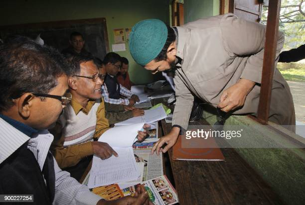 A man looks for his name on the first draft of the National Register of Citizens in Guwahati in the Indian state of Assam on January 1 2018 Around 13...