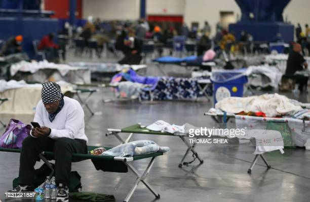 Man looks for information on his cell phone as he rest at the George R. Brown Convention Center on February 17 in Houston, Texas. - A winter storm...