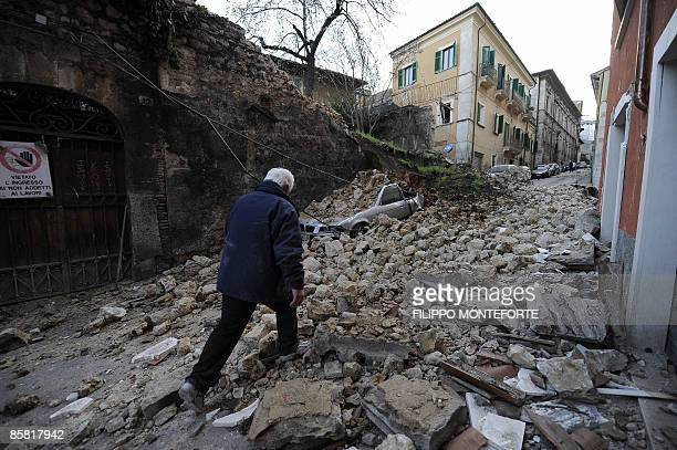A man looks for relatives in the ruins of a collapsed house on April 6 2009 in the center of the Abruzzo capital L'Aquila the epicenter of an...