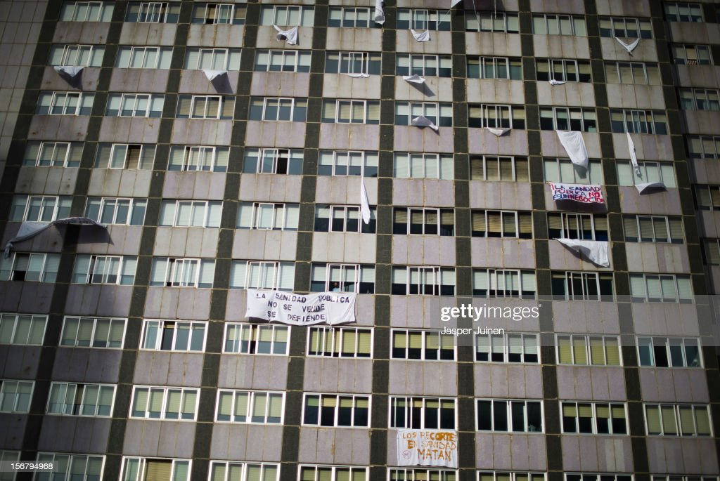 A man looks from a window as banners hang from La Paz hospital on November 21, 2012 in Madrid, Spain. Doctors and nurses in the Spanish capital are preparing for a four day strike to protest against the privatisation of some parts of Spain's national health service.