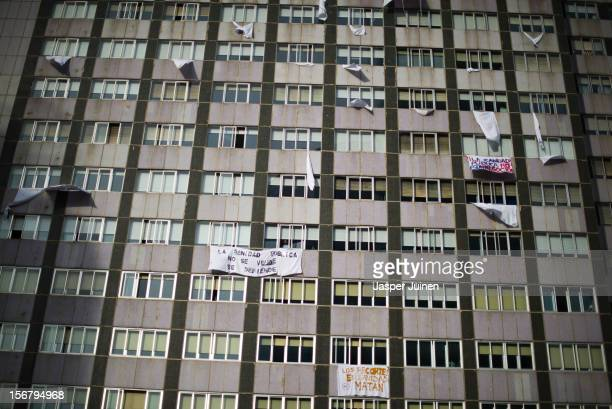 A man looks from a window as banners hang from La Paz hospital on November 21 2012 in Madrid Spain Doctors and nurses in the Spanish capital are...