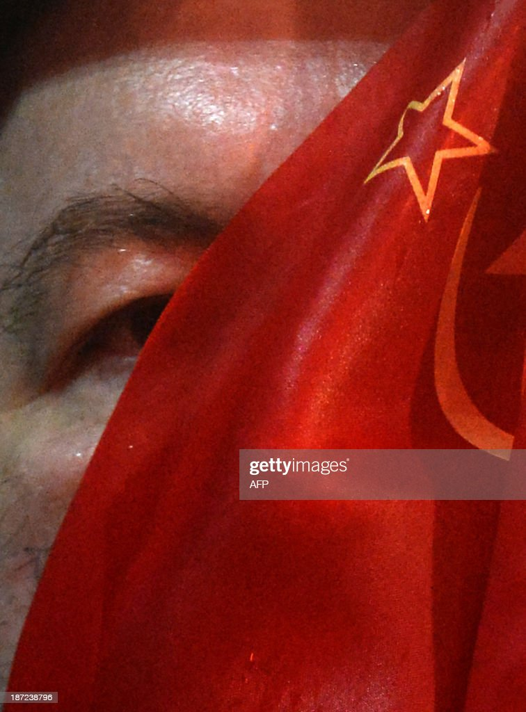 A man looks from behind a Soviet flag as he attends a rally of Russian communist party activists and supporters to mark the 96th anniversary of the 1917 Russia's Bolshevik Revolution in central Moscow on November 7, 2013.