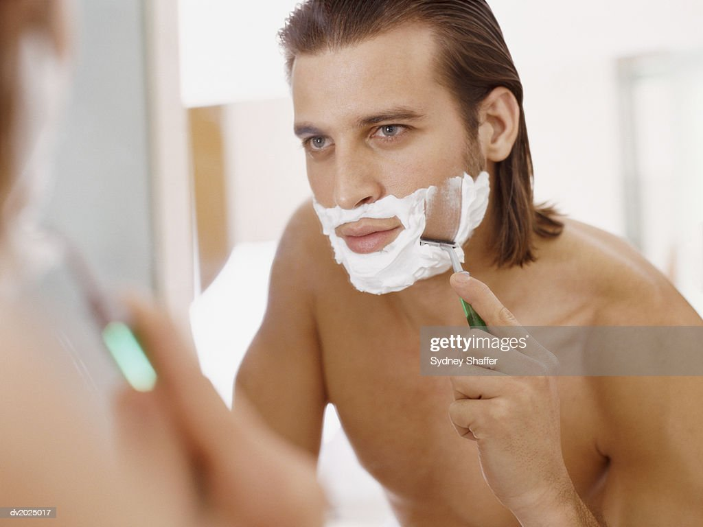 Man Looks in a Bathroom Mirror, Shaving His Chin With Shaving Foam and a Razor : Stock Photo